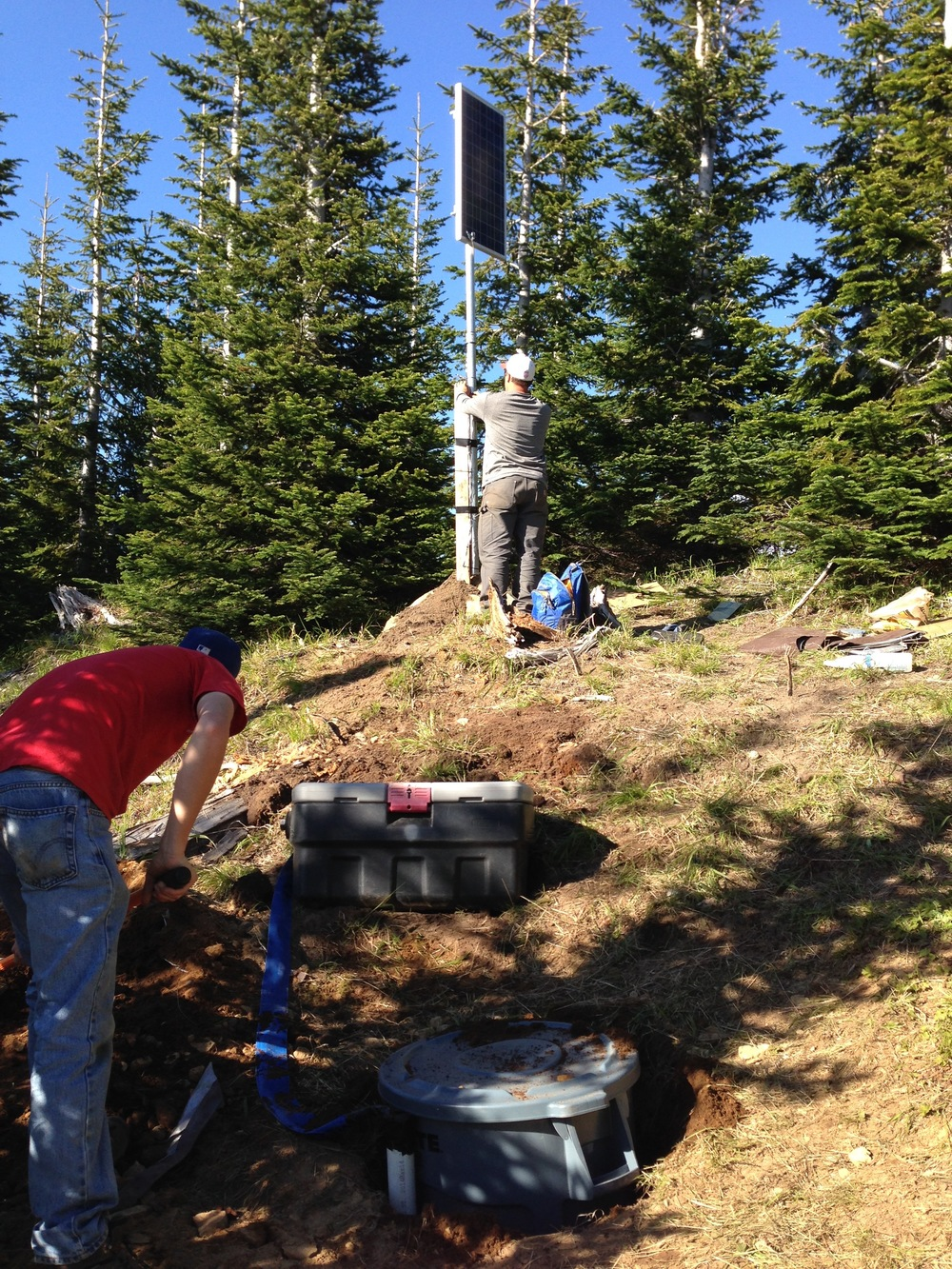 Installing a station near Mt. St. Helens, WA, in 2014. In the background Mark is securing the solar panel, while in the foreground Dylan is filling back in the hole with the sensor (attached via blue cables to the power/digitizer package in the middle).
