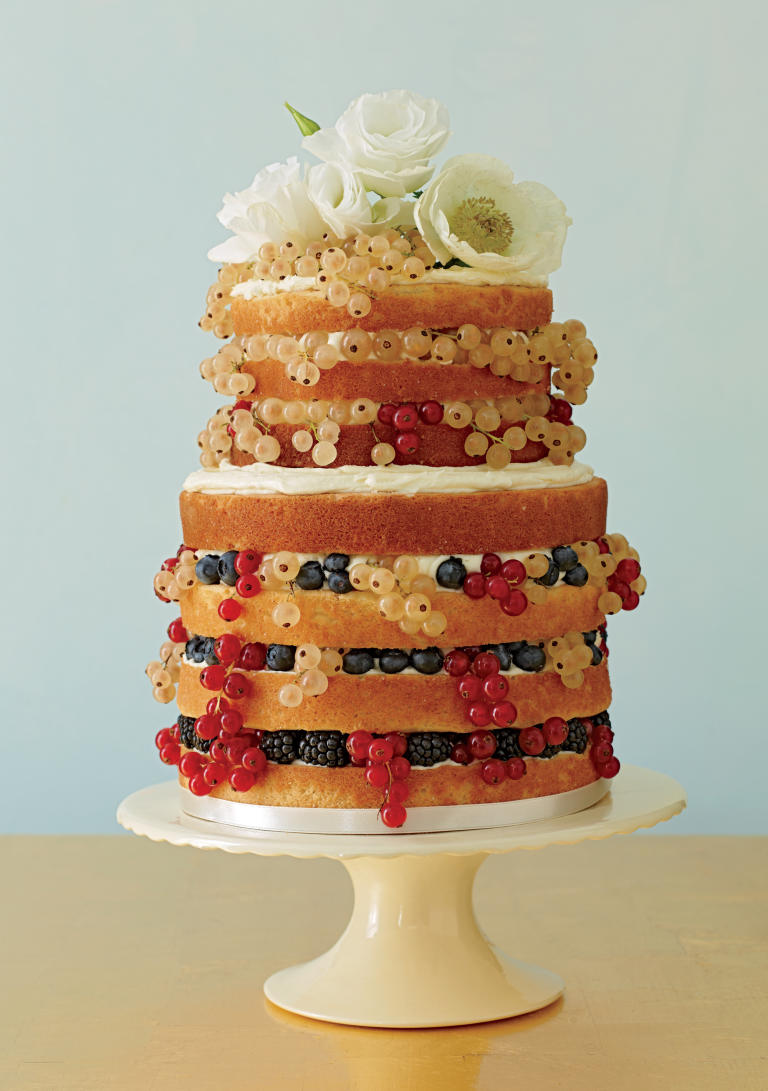 Two tiered naked cake with white flowers and mixed berries, as seen in The Knot magazine