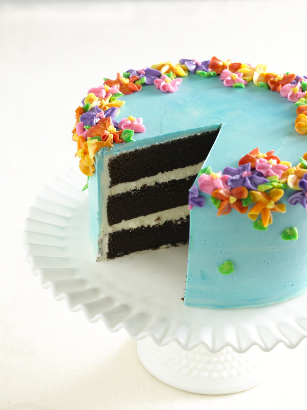 Turquoise frosted chocolate cake with vibrant flowers around the top