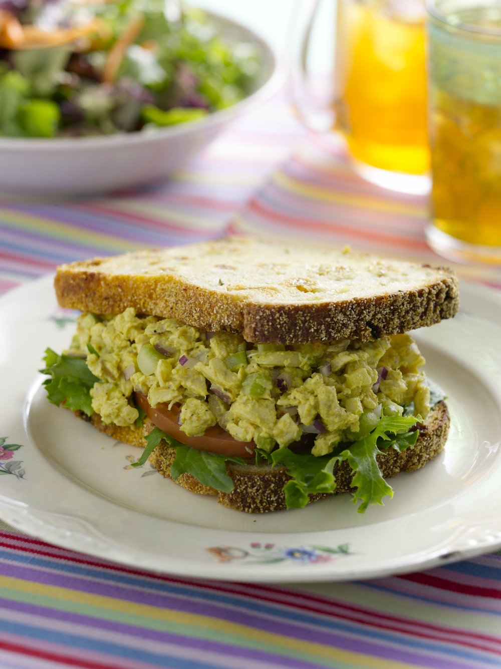 Curried Chicken Salad Sandwich, with red onion, celery, granny smith apple, greens and tomato slices on golden raisin- fennel-semolina bread.