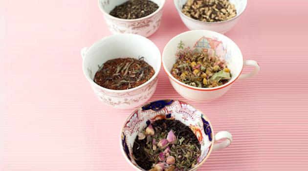 Assorted loose leaf teas, displayed in tea cups.