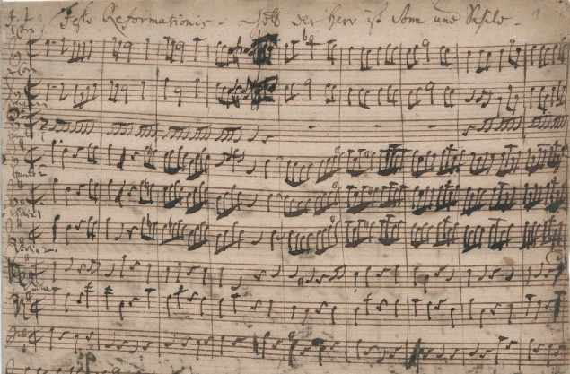 The first nine bars of the manuscript of Cantata 79, with the horn parts at the top, and above that, in Bach's handwriting:  Festo Reformationis / Gott der Herr ist Sonn und Schild