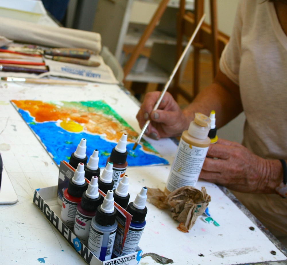 Here a student is using both Fluid and High Flow Acrylics by Golden to create her landscape painting.