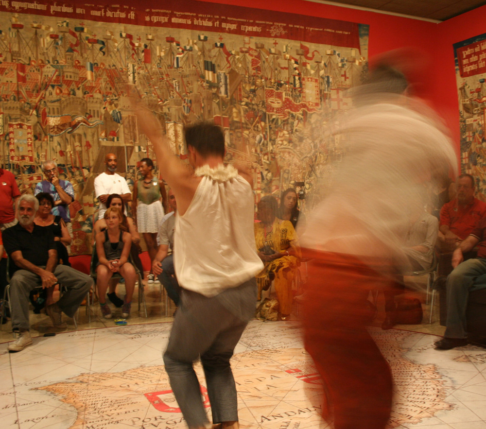 A view of the dance performance using the tapestry with the Pastrana Tapestry hanging on the wall in the background.