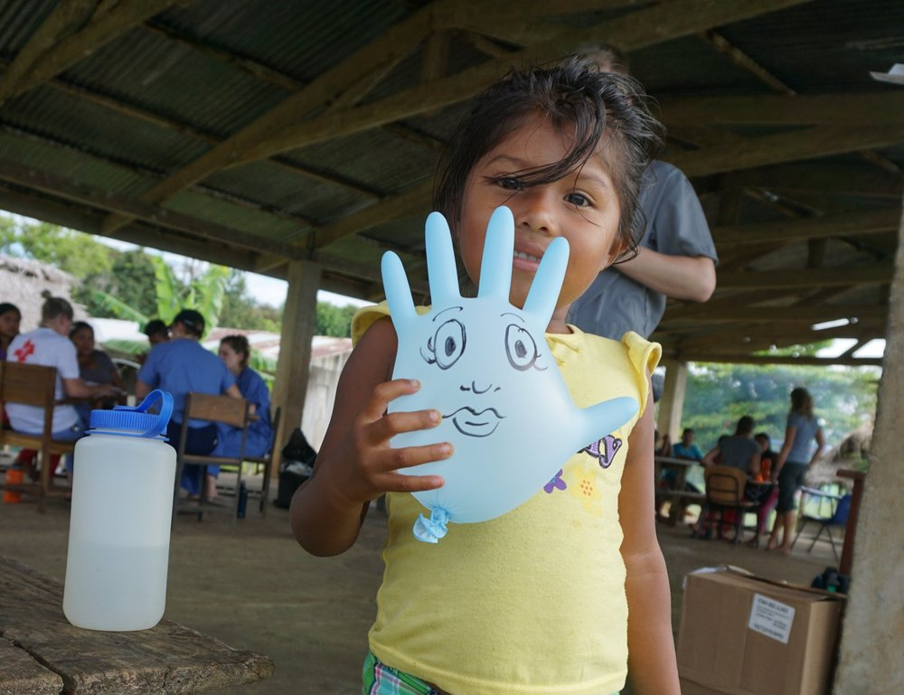 A glove balloon is sometimes the best toy to calm a child during their exam. This child shows off her balloon afterwards.