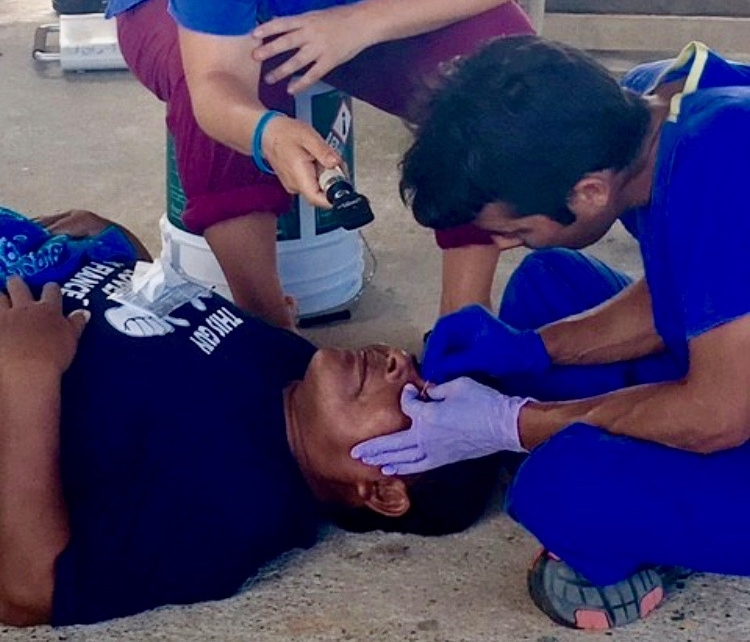 Lead Medical Provider, Luis, wears gloves as he carefully removes a splinter from a patient's eye.