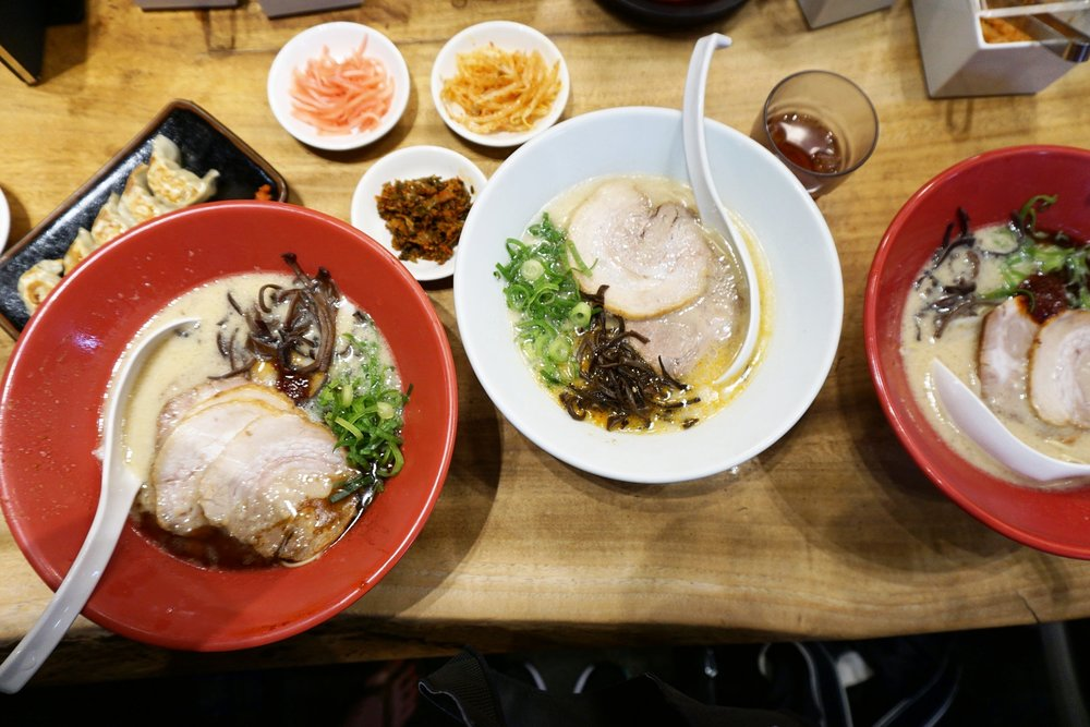Akamaru ramen (red bowl) and shiromaru ramen (white bowl) along with gyozas and side dishes of pickles