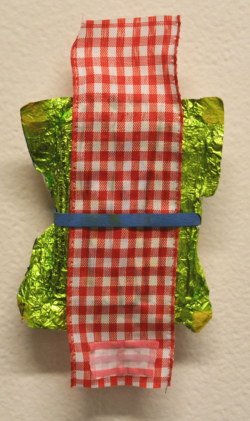 Wire edged ribbon, fabric, rubberband, foil, and oil paint on wood