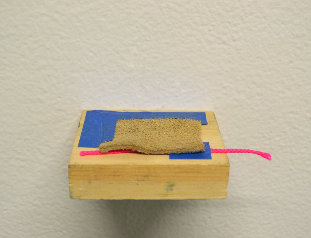 Painter's tape, suede, and plastic cord on wood