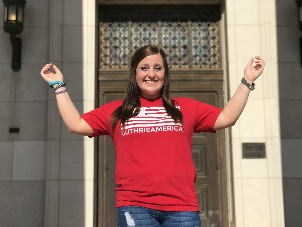 mollie with hands up in guthrie america tee shirt.jpg