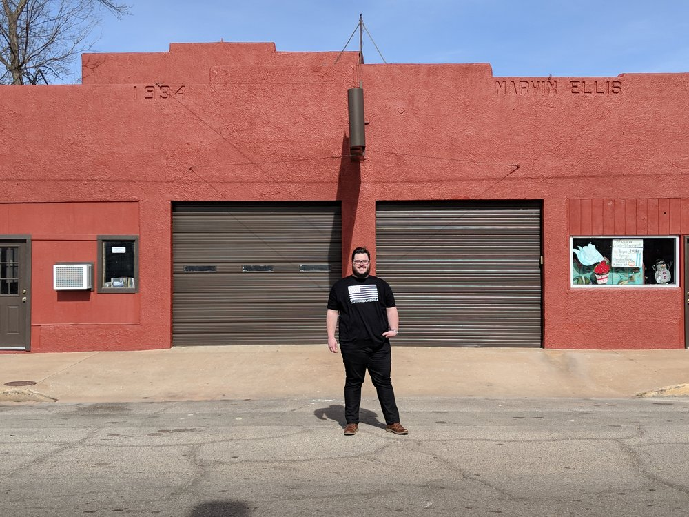 jeffery in front of red building in downtown guthrie america.jpg