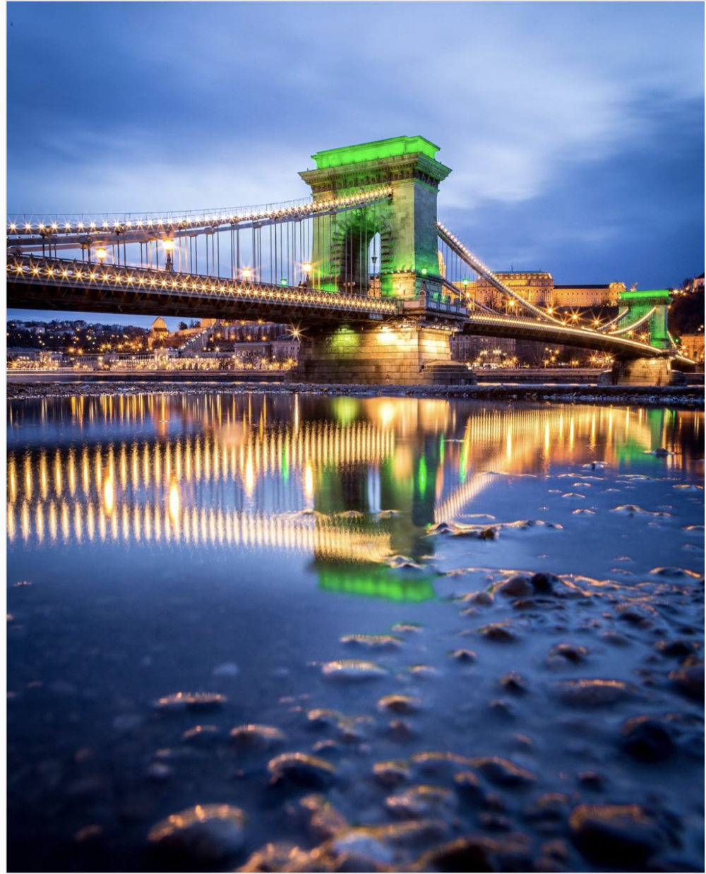 Using a puddle to photograph reflections of the Chain Bridge, Budapest, Hungary