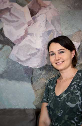 Photo of Elena Skvirskaya, oil painting in the background