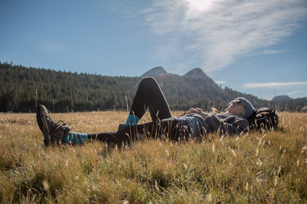 "Laying next to the river bed in Tuolumne Meadows, Yosemite National Park. ""Within Tuolumne Meadows, visitors see the Tuolumne River meandering quietly through its meadow channel and cascading over the granite river bottom against a backdrop of rugged mountain peaks and glacially carved domes."" (Source:  Tuolumne Meadows )"