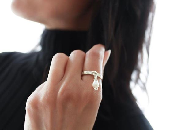 The  Cielo Sterling Silver Ring  comes with a small pearl charm attached.