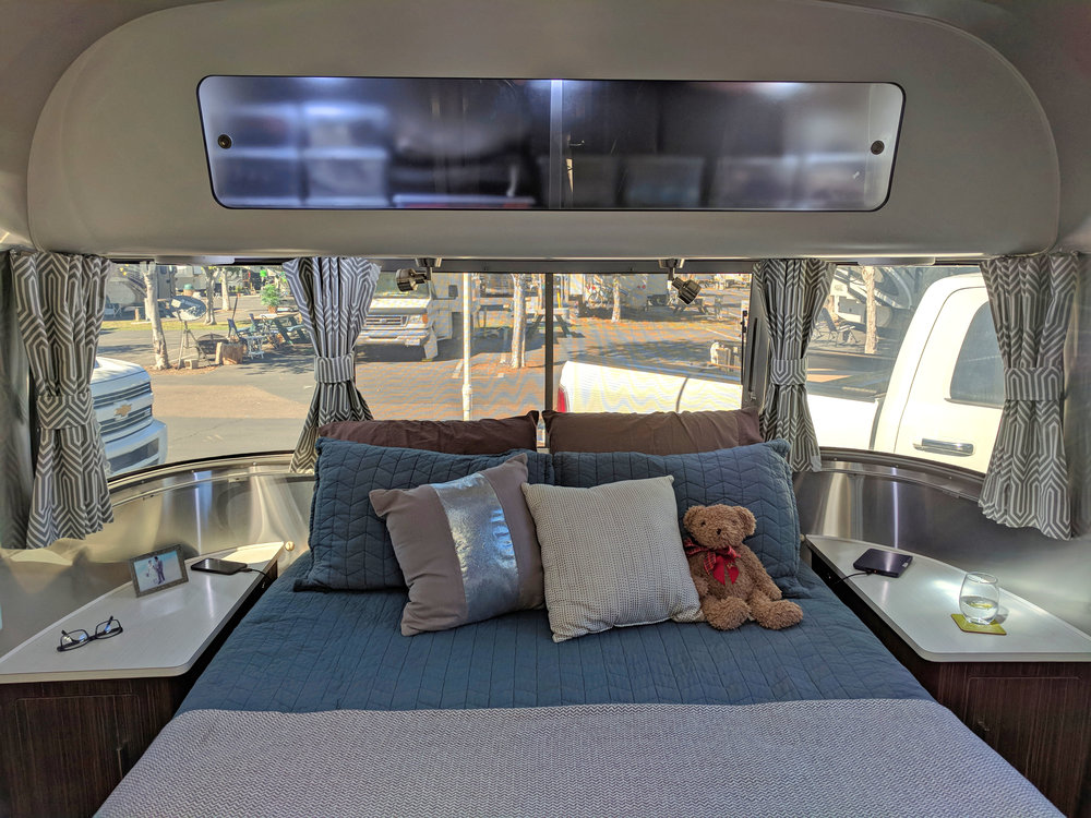 At the front of the Airstream is our bedroom. We have a walk around queen bed with a pillow top mattress. It's very comfy! Underneath the bed there is considerable storage. Above we store underwear, workout clothes, socks etc.
