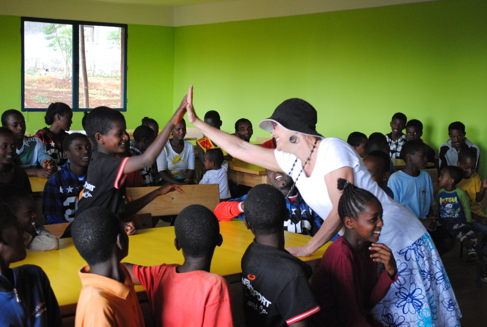 Val Easton, a volunteer for Mothers with a Heart for Ethiopia, gives a high-five to a child in the Busajo program in Soddo, Ethiopia after doing a fun singalong with the kids.