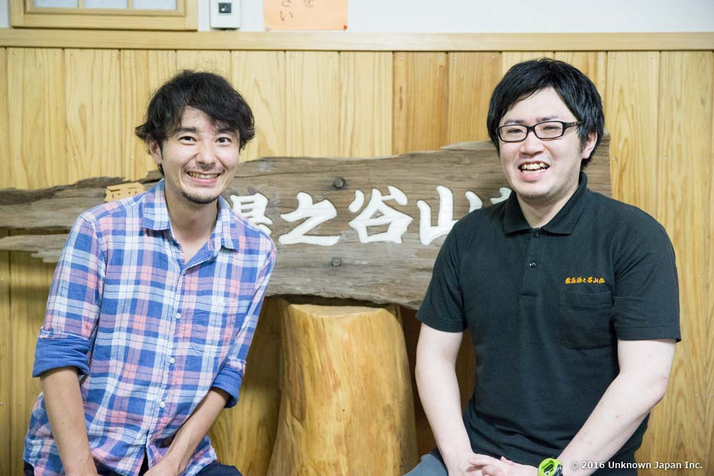 霧島湯之谷山荘4代目の馬場雄二郎さんと玄関にある看板の前で撮影