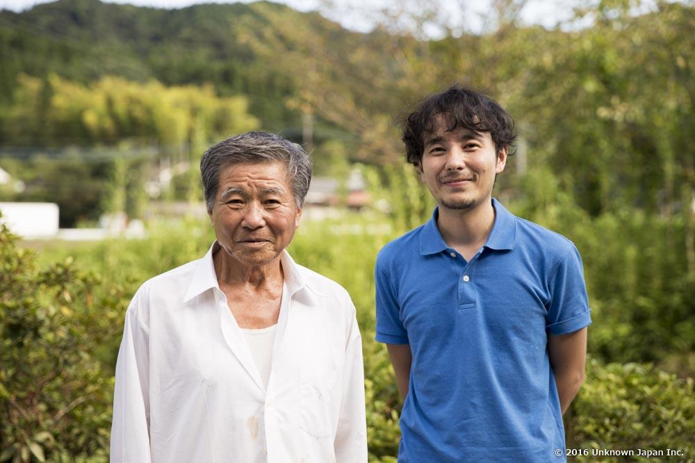 オーナーの永盛敏さんと建物の目の前に広がる田園風景をバックに撮影
