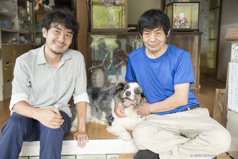 栗野岳温泉4代目の永峯周作さんと犬のレオと受付前で撮影