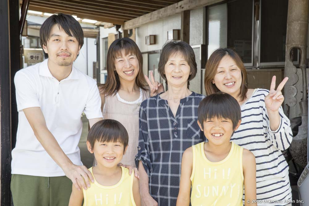 オーナーの今村マスエさん(後列右から2人目)のご家族と入口の前で撮影