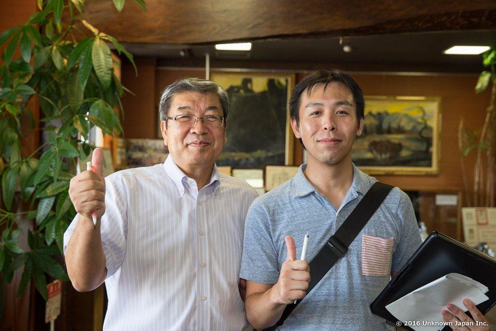 堤温泉を運営する「繊月酒造」常務の田中泰昭さんと酒蔵にある試飲スペースで撮影