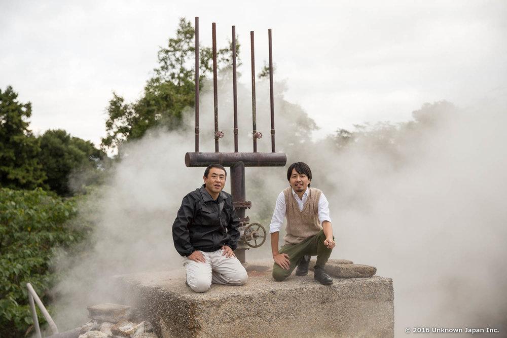 オーナーの岸本勝仁さんと泉源地にあるフォーク型の消音器の上で撮影