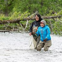 "Guide Academy student Tatyana successfully coaches her ""client"" into her first fish on a fly rod."