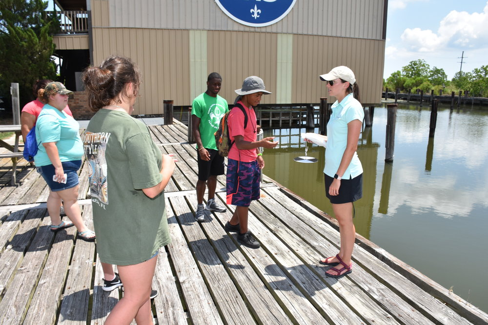 Corinne Bird, LSU AgCenter extension associate for youth wetlands, prepares to teach a lesson on water turbidity during a 4-H wetlands camp at Chef Menteur Pass in Orleans Parish. The camp was held July 11-14 and taught the youth about ecosystems, wetland habitats, species diversity and food web relationships. Photo by Johnny Morgan/LSU AgCenter