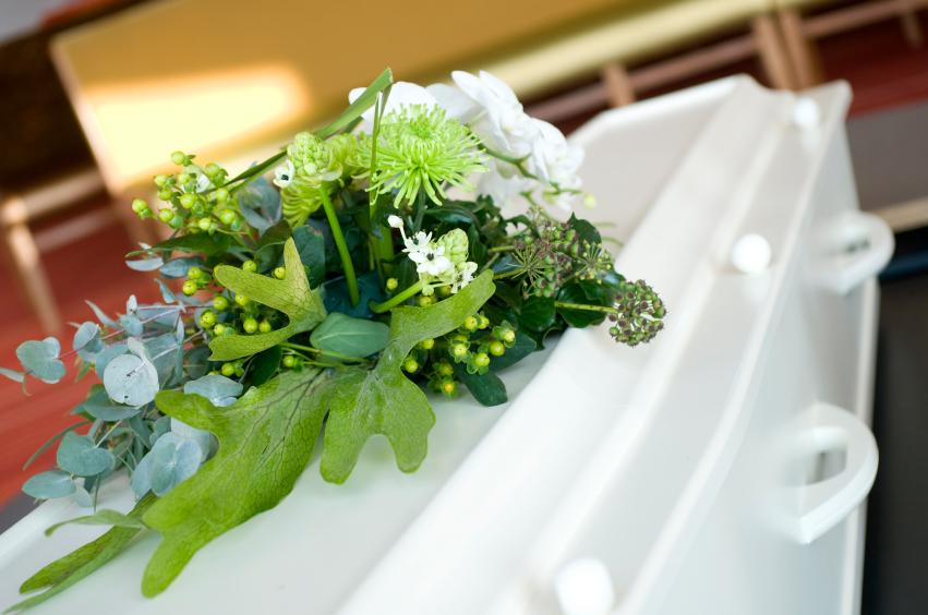 SAGA Begravelsesbyrå hvit kiste med bårebukett.jpg