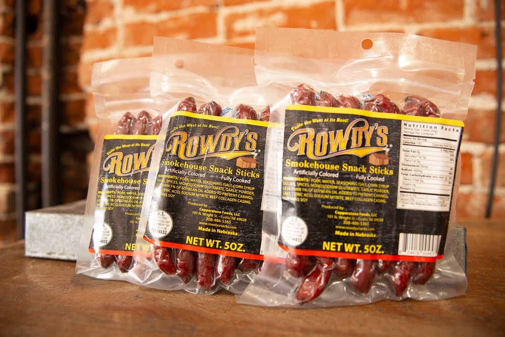 Rowdy's Smokehouse Snack Sticks  - New to the Rowdy's family! These sticks are a 100% Nebraska pork product. Naturally hardwood smoked in our Nebraska smokehouse. This is a fairly mild snack…in other words, a snack everyone will enjoy!   $6.49 / 5 oz bag (7 sticks)