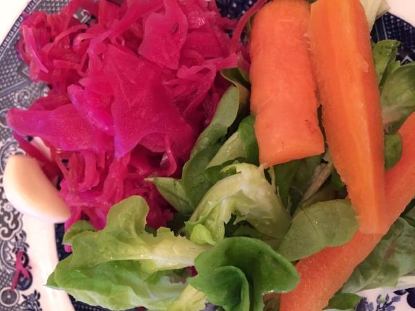 Fermentert rødkål, gulrotstaver, hvitløk - på en seng av grønne blader.