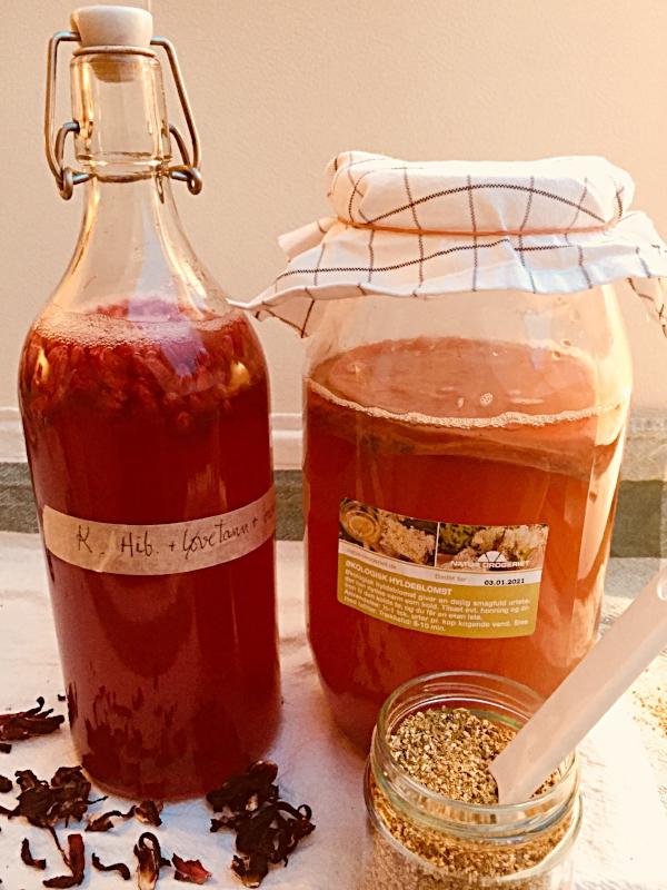 I flasken er det kombucha som er brygget med hibiskus, løvetann og brennesle. Etterfermenteres her med litt bringebær. I glasset til høyre er det hibiskus og hylleblomst. En nydelig blanding som anbefales!