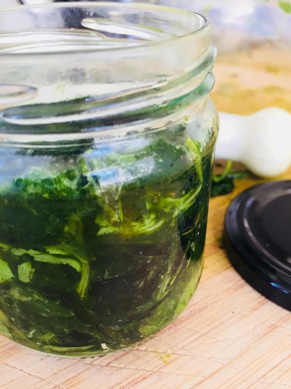 Massevis av grønne blader er stampet ned i et lite glass.