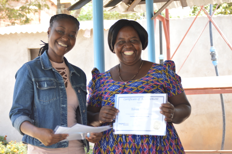 Bibian from CHACOP School proudly showing off her certificate at the Graduation Ceremony
