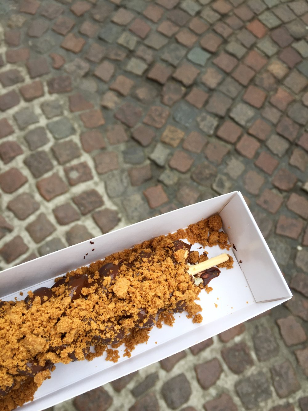 waffle on a stick dipped in chocolate with speculoos cookies (Bruges)