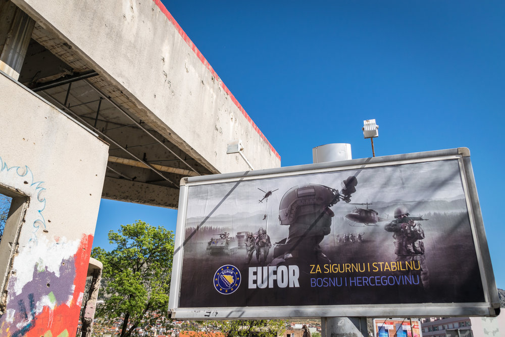 "Sign outside of the Sniper Tower: ""For a secure and stable Bosnia and Herzegovina"" reads the sign selling EUFOR Althea, a military deployment that oversees the implementation of the Dayton Agreement; just my humble opinion, I don't think more guns and fighting will stabilize this war-torn community"
