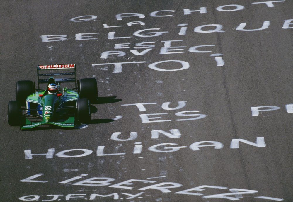 Michael Schumacher flies over pro-Gachot graffiti left by disgruntled Belgian fans.