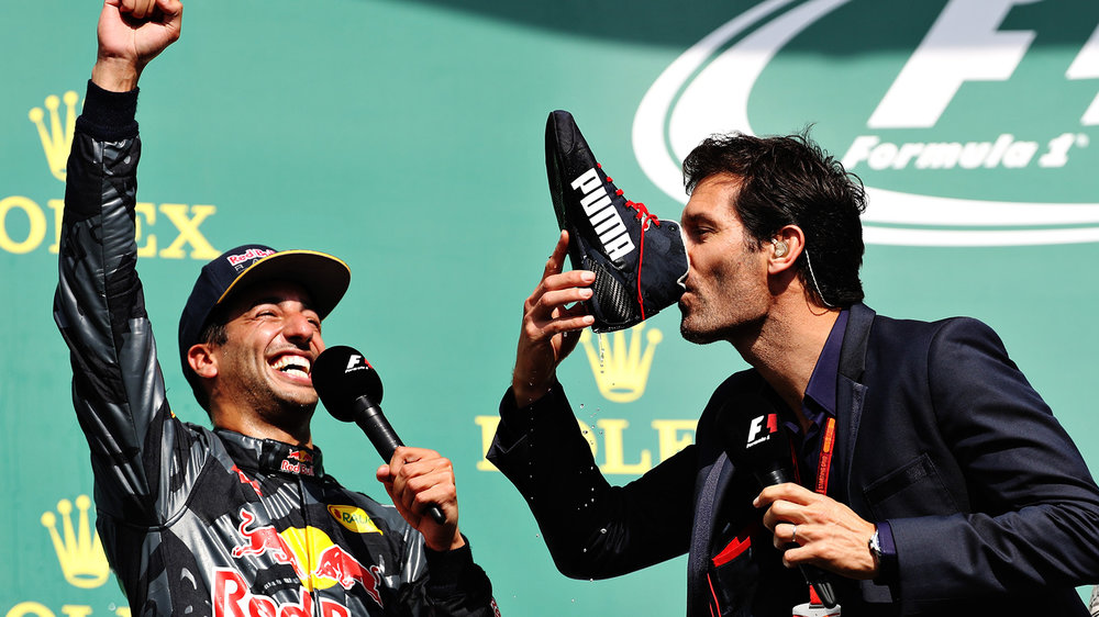 Mark Webber does a shoey from Daniel Ricciardo's boot at Spa