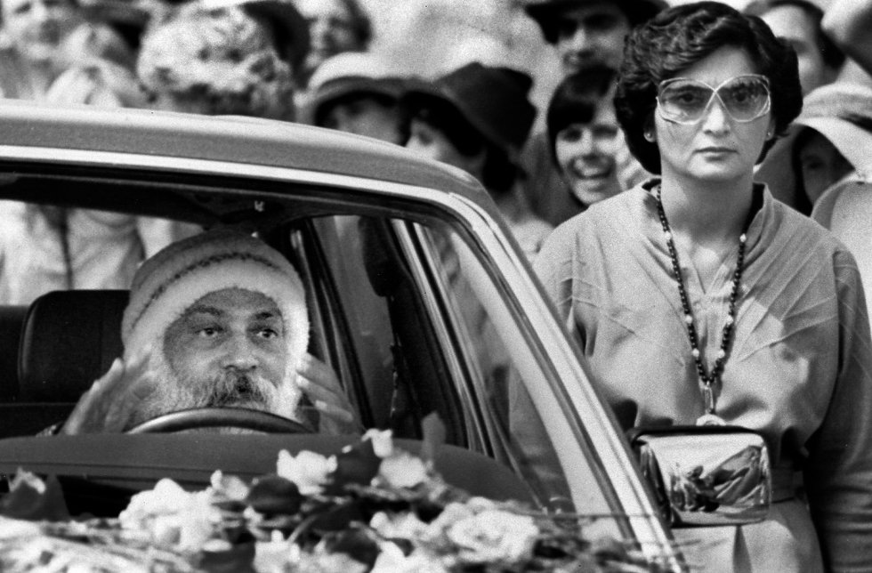 The Bhagwan driving alongside his secretary, Ma Anand Sheela.