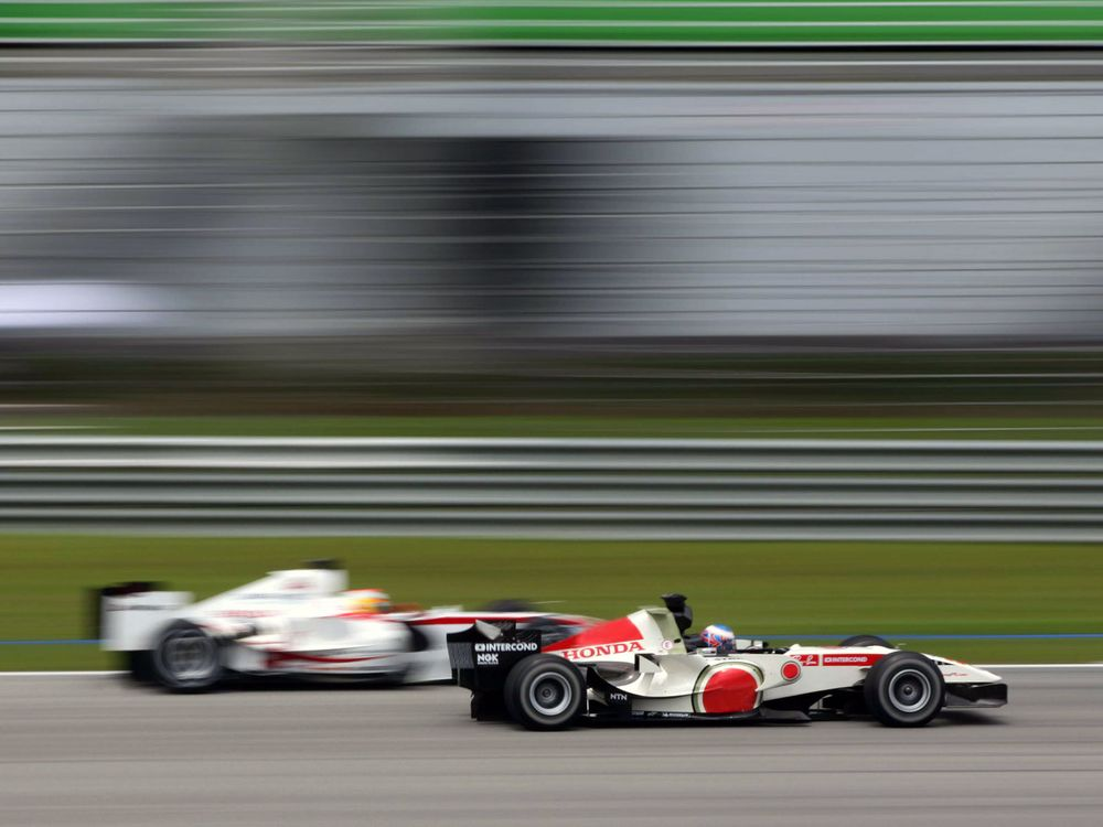 The Honda of Jenson Button blasting pass the Super Aguri of Yuji Ide at Sepang.