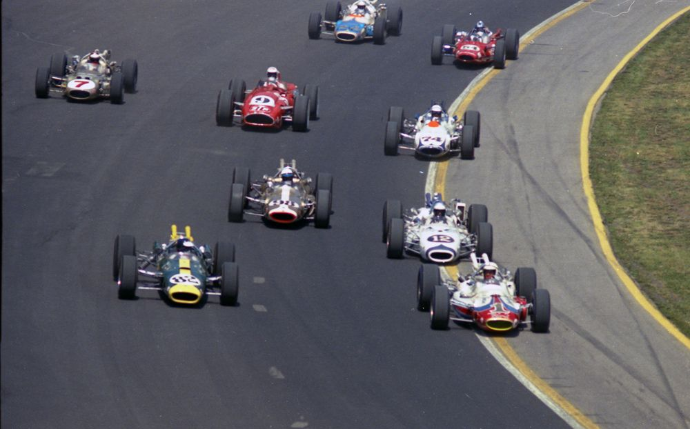 Jim Clark (#82) battling A.J. Foyt (#1) for the lead. The offset suspension of the Lotus 38 is clearly visible here.