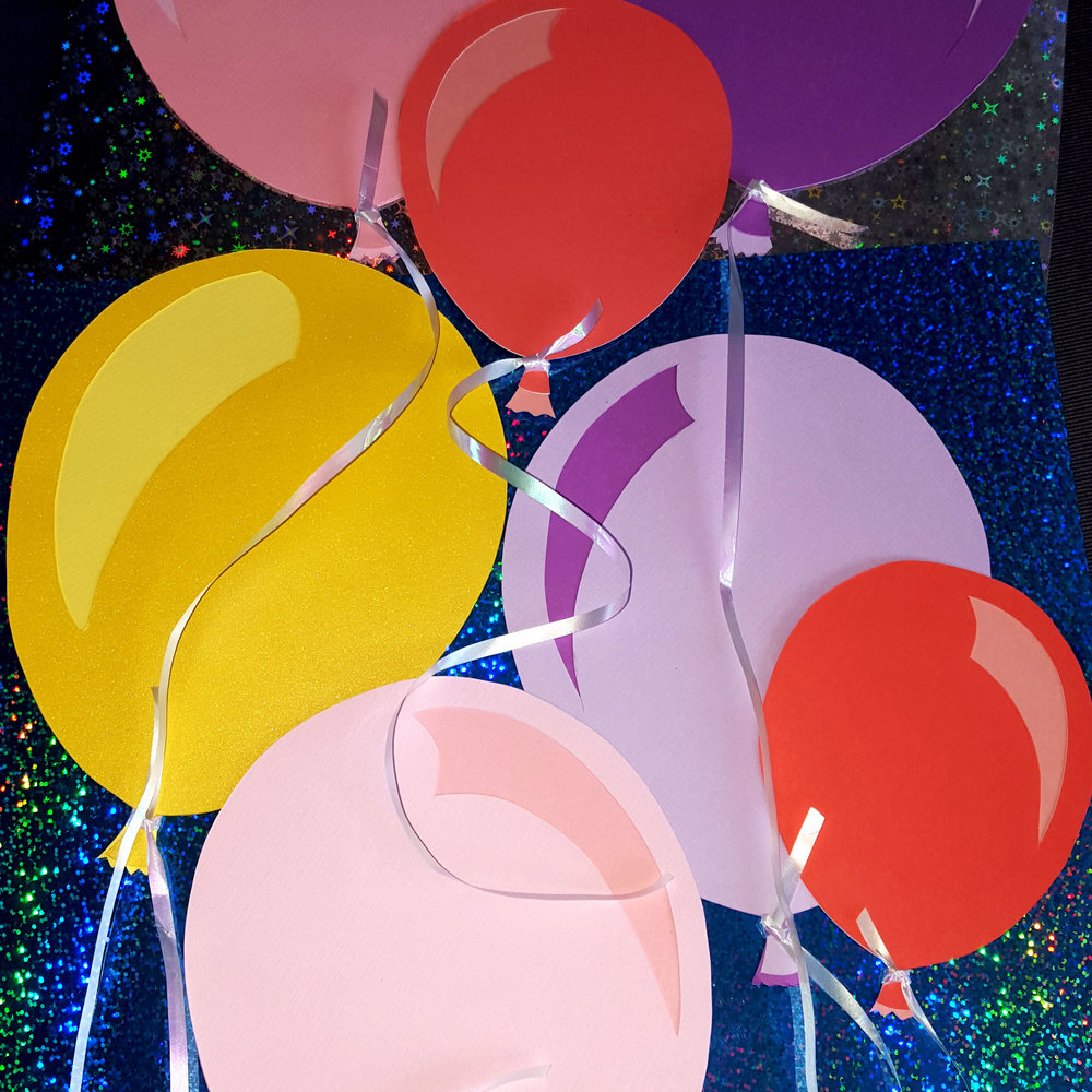 Two layers of card stock, hand-cut, for each balloon. Tied with holographic ribbon. Used for gift tags/embellishments and party decor.