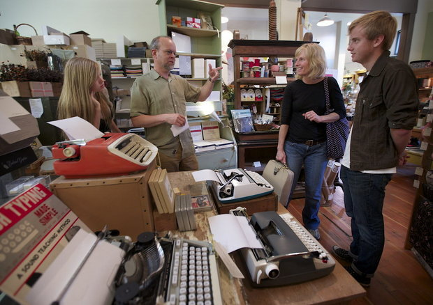 "Oblation Papers & Press co-owner Ron Rich (second from left) talks with Cindy Bilotti (second from right), who, with her son, Ben, bought a refurbished Czechoslovakian Consul typewriter during the northwest Portland store's ""type-in"" on Sunday, recognizing International Typewriter Day. (Randy L. Rasmussen/The Oregonian)"