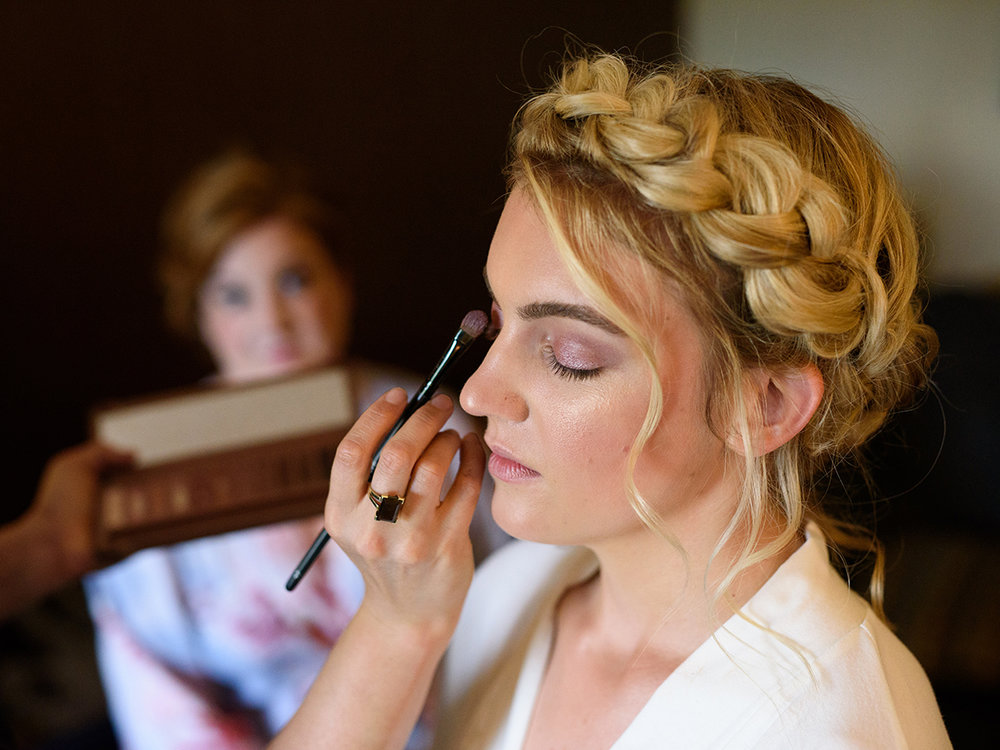 A bride gets her makeup done (by NylaGray Photography)