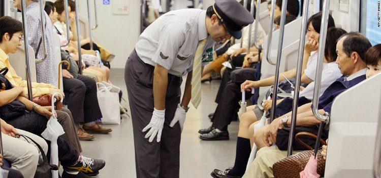 Worker apologizing for train delay, Japan