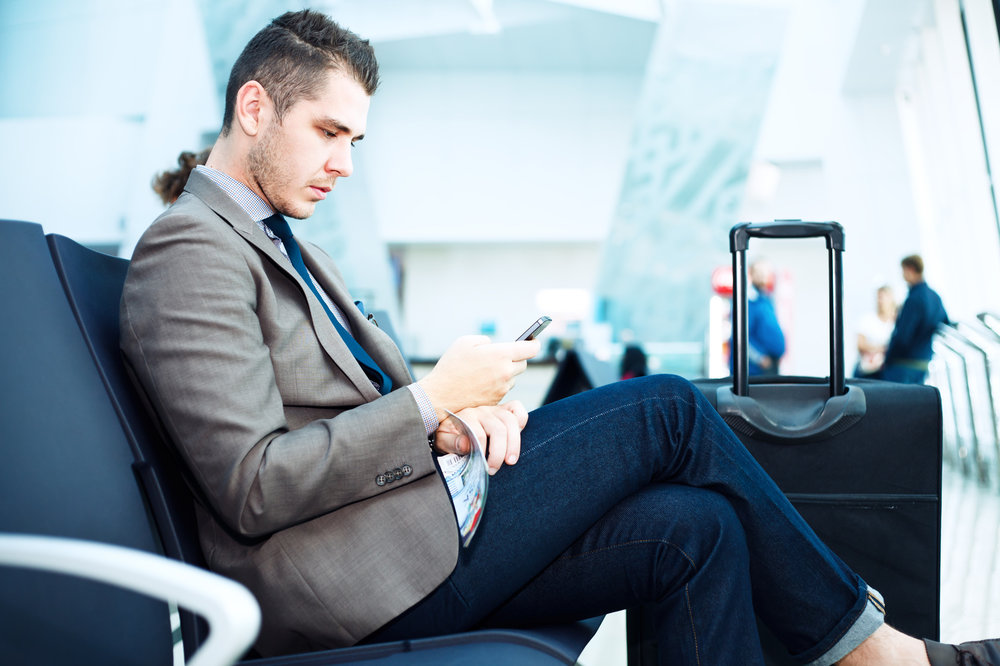 Traveler with mobile at airport