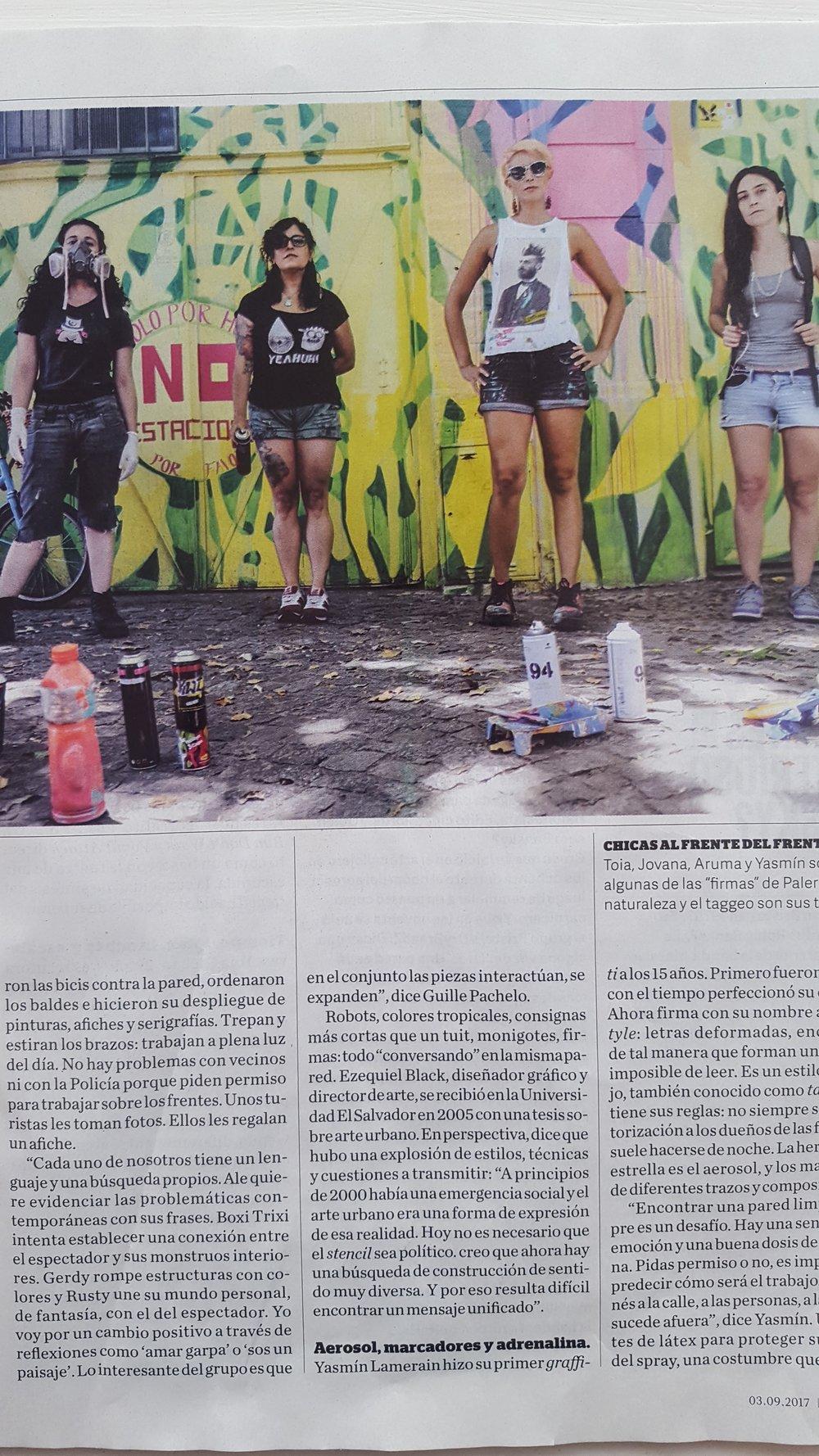 Foto de le edición impresa de la nota en la Revista Viva. Yasmín, Jovana, Toia y Aruma (izq a der) frente a un mural de Toia Grehan.