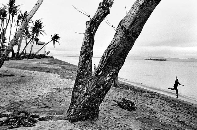 Residents frolick by the shores of Tacloban bay, the same area where the tidal surge claimed the lives of residents living near the water.  The change in earth's temperature is predicted to cause stronger typhoons like Haiyan. Every year, as more people face these issues, SIGNOS illustrates the new norm, a dark sign of things to come. Climate change does not happen in isolation. The signs are clear and there's no denying what the future generations will be facing.  An outtake from forthcoming book Signos by Veejay Villafranca (@veejayvillafranca) published by MAPA Books.  #signos #veejayvillafranca #mapabooks #everydayphilippines #yolandaph #haiyanph  #everydayclimatechange #everydayeverywhere #visayas #philippines #climatechange #climatechangeisreal #photobooks #artph #contemporaryphotography