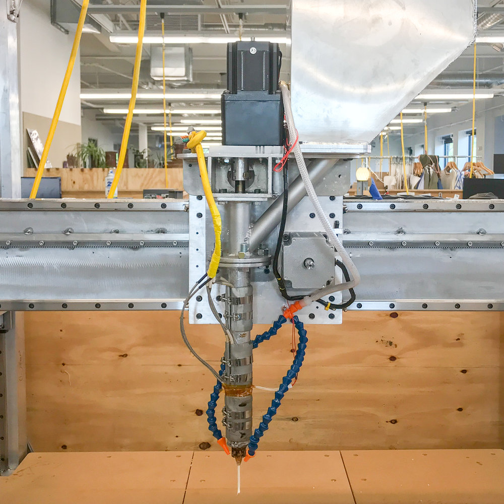 We began the design of the entire V2 machine by designing the V2 pellet extruder first, then designing and building a motion platform to support it. This version is a 10x performance improvement over V1, weighing roughly 30lbs and capable of processing 5lbs of plastic per hour.